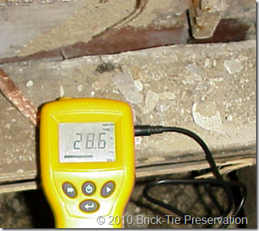 Electrical moisture meter reading 'fibre saturation' content in floor timbers in a hpouse in Leeds