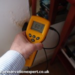 An electronic moisture meter reads qualitative on plaster